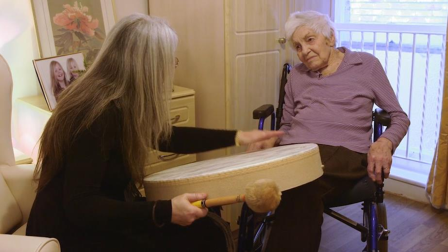 Evelyn alongside a dementia patient, using instruments to develop communication