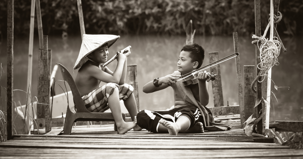 Children playing with instruments sat next to each other